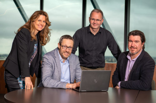 Four smiling cancer research executives with a computer in the foreground